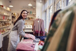 Female Small Business Owner Arranges Stock In Window Display