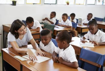 Volunteer teacher helping school kids at their desks